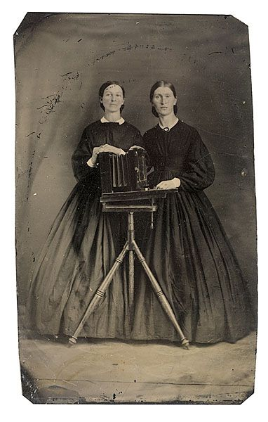 Tintype of Women Posing with Camera - Cowan's Auctions    ca 1870s uncased sixth-plate tintype, 2.5 x 4.2 in., with clipped corners. The women pose with a camera box, seated atop a daguerreian tripod