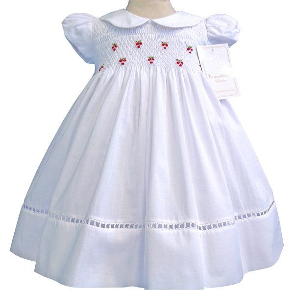 Our Alicia girls elegant white dress is beautifully smocked across the bodice in white with red embroidered roses, little short sleeves and Peter Pan collar add elegance, to finish the skirt is adorne