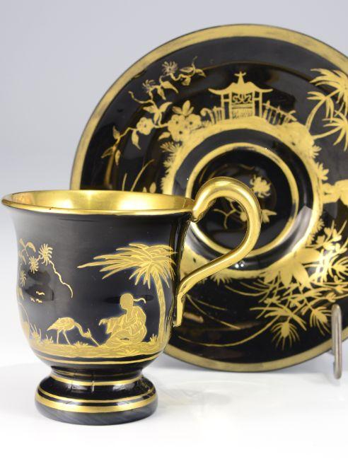 Šálek s podšálkem  Jižní Čechy, Buquoyské sklárny, 1820–1840 Zvonovitý koflík na vyšší patce, s převýšeným páskovým uchem a miskou, černé hyalitové sklo, broušené, na plášti obou kusů jsou v malbě matným a leštěným zlatem provedeny jemné chinoiserní motivy  V. šálku 9 cm, Ø talířku 14,4 cm.