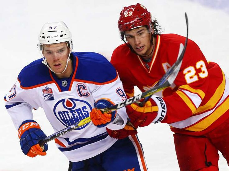 Edmonton Oilers Connor McDavid battles for the puck against Sean Monahan of the Calgary Flames during NHL hockey in Calgary, Alta., on Friday, October 14, 2016.