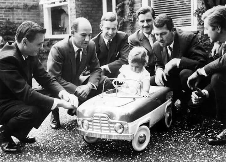 1961 (July) : Baby Damon Hill in his toy car at his christening watched by (from left to right) Bruce McLaren, Stirling Moss, Tony Brooks, his father Graham Hill, Jo Bonnier and Wolfgang Von-Trips. (ph: pinterest.com)