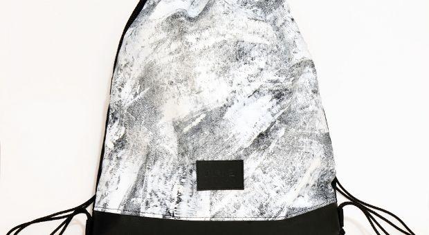Tornazsák egyedi, kézzel festett fehérmintával. Nők és férfiak is bátran hordhatják. A minta egyedi, kézzel készült, így némileg eltérhet a képen látottól.  Anyag: vászon, textilbőr, poliészter zsinór  Méret:46 x 40 cm   Szín: fekete-fehér