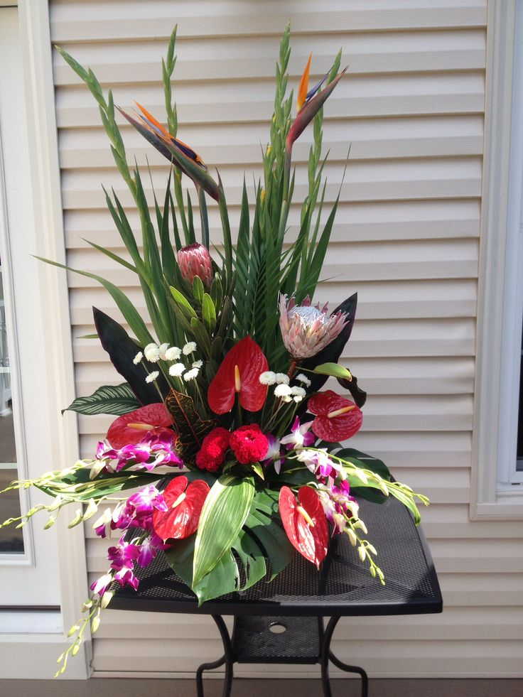 Protea, birds of paradise, orchids, calla lilies, button mums, anthurium, and gladiolus.