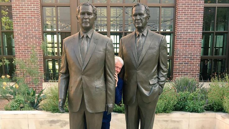 Bill Clinton plays presidential peek-a-boo between two Bush statues
