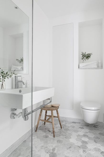 Dream bathroom. White walls, wall-mounted sink with towel bar, marble flooring, and natural accents. Add a tub/shower combo with marble subway tiles, a shelf under the sink, and a medicine cabinet and I'm in heaven.