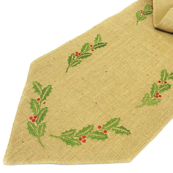 Gold colored threading is weaved into the burlap fabric and stitched around the mistletoe pattern, creating a subtle yet elegant shimmer.