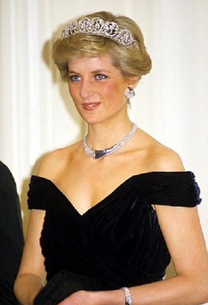 Princess Diana of Wales attends a state banquet in Bonn, Germany in November 1987. She wears a spectacular Victor Edelstein deep blue silk-velvet dinner dress with off-the-shoulder straps and a slight bustle. The Princess also wears, the matching set of jewels presented to her by the Sultan of Oman in 1986. The Spencer family tiara adds an extra touch of sophistication.