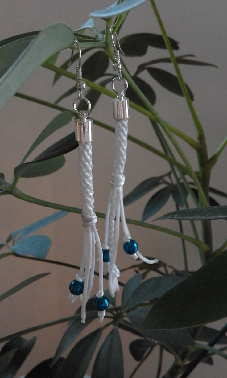 A pair of white kumihimo earrings with blue beads.