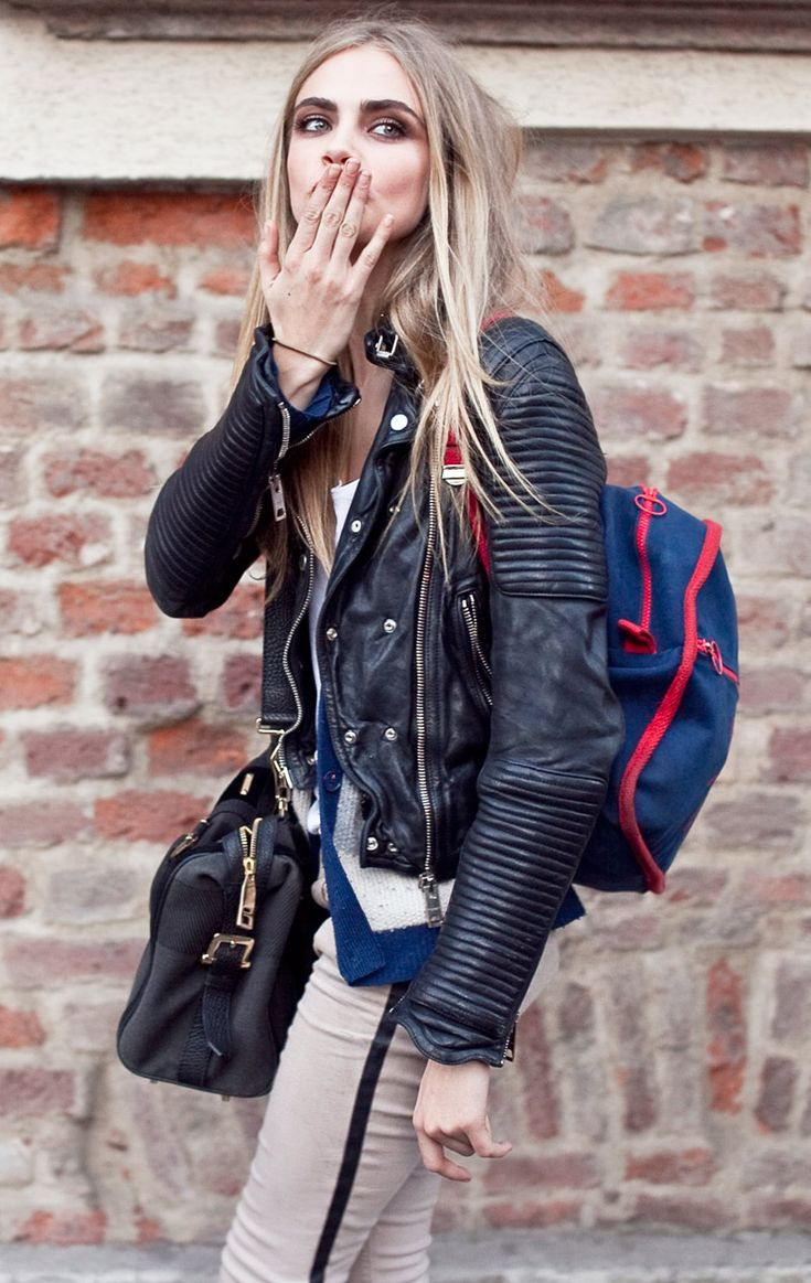 Cara Delevingne is perfect. Black leather moto jacket, backpack, black leather bag and white pants with black piping. Also gorgeous smokey eyes.