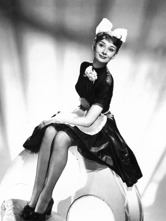 A young and darling Audrey Hepburn wearing a French maid outfit (1950s).
