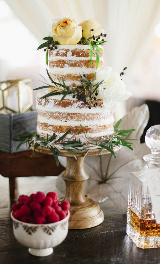 Breathtaking two tier boho wedding cake topped with yellow flowers; Featured Photographer: Natalie Franke Photography