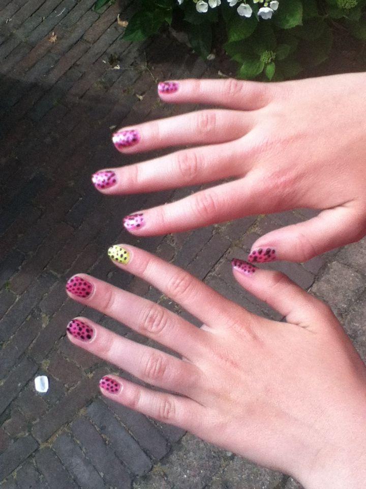 Een gele en negen roze nagels met zwarte stippen.