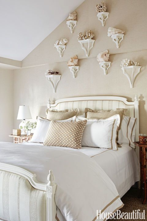 In the guest bedroom, an assortment of brackets unifies an uneven wall; herringbone wallpaper by Ralph Lauren Home and faux bamboo nightstands by Williams-Sonoma Home add textural depth to the cozy space; the bed is upholstered in a Carolina Irving Textiles fabric.