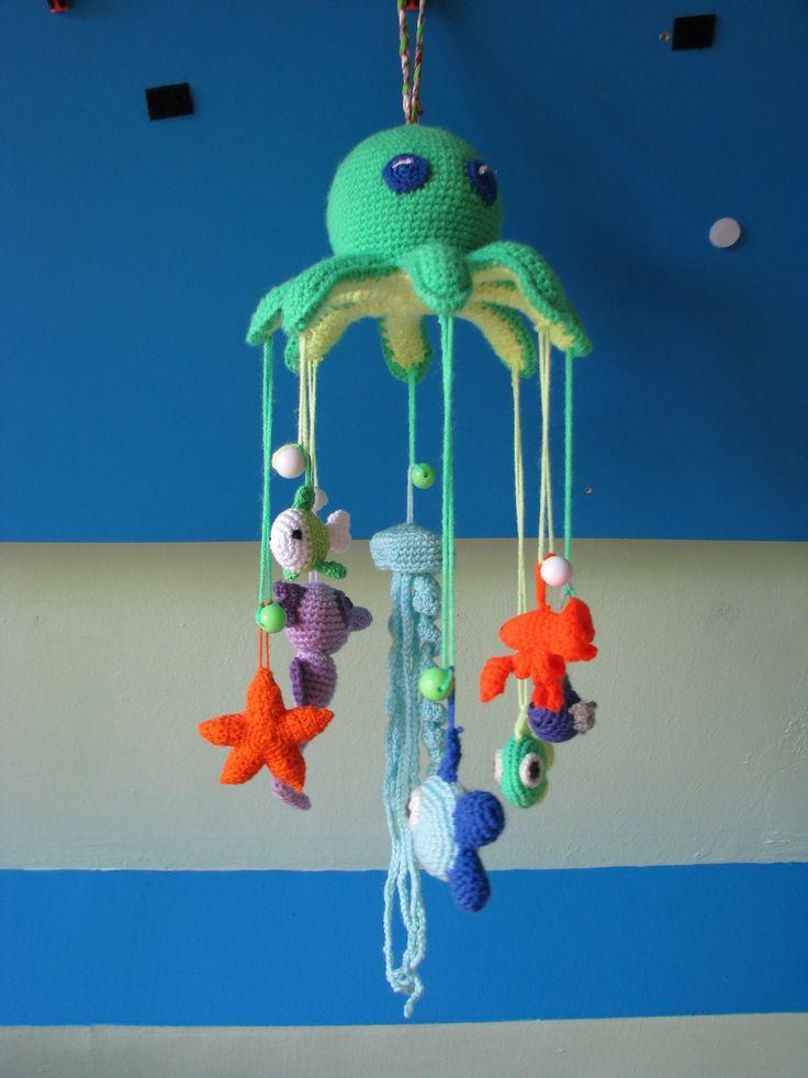 octopus mobile. Patroon was gevonden bij de starfish. Zelf extra metaaldraad ingezet voor de stevigheid van de mobiel. Aan de draadjes hangt een ronde kraal, zodat het handig is met de diertjes eronder te hangen en te veranderen.