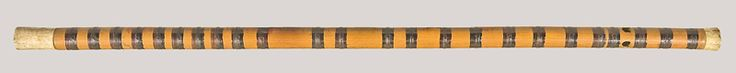Qudi, China, early 20th century. Transverse, bamboo flute with bone end-caps. Inscribed in red ink with imitation Chinese characters. Twenty-four bands of silk thread coated with black lacquer. Traditionally, a thin, vibrating membrane (dimo) is peeled from the interior of a bamboo stalk and adhered to the flute using peach sap, giving the qudi its characteristic buzzing sound. Longer flutes like this are often played in the kunqu opera, where they are called kundi.