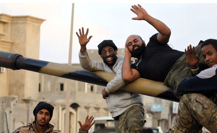 Fighters rest on a big gun and wave at the camera in Benghazi, Libya - Saturday 14 January 2017