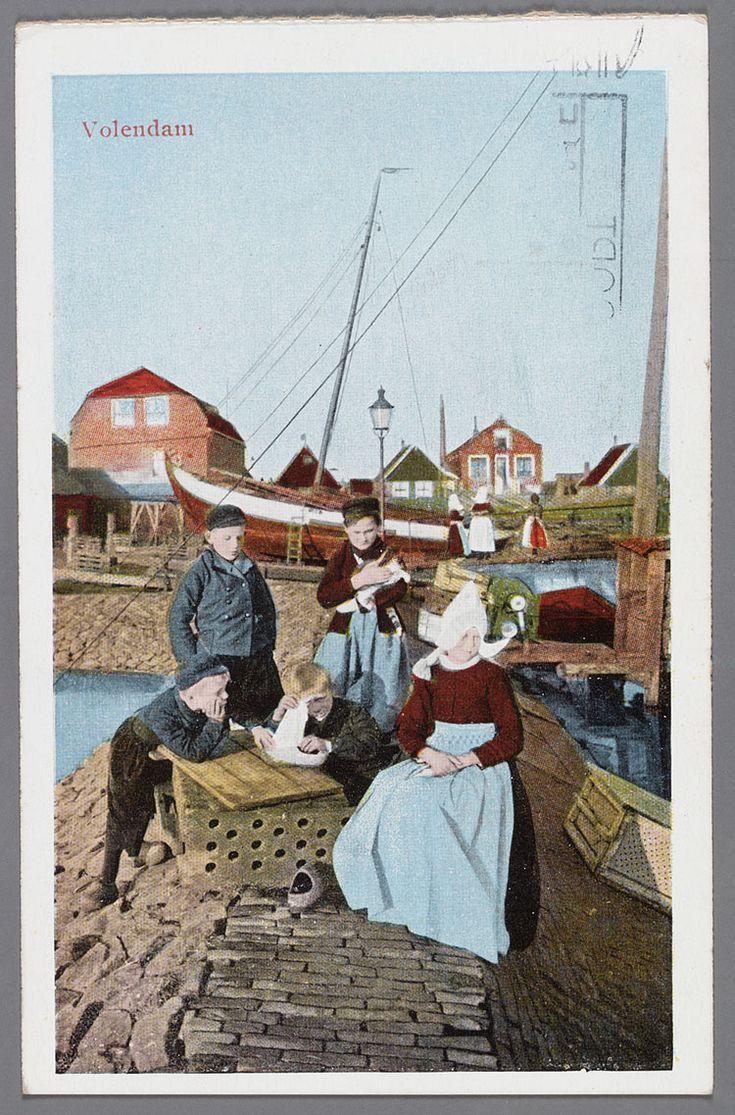 Vijf kinderen op een dam bij de haven. Twee jongens leunen op een viskaar en spelen met een klompbootje. Op de achtergrond een botter op de helling. 1940-1946 #NoordHolland #Volendam