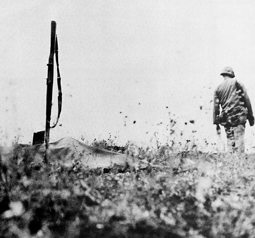 A marine moves on to catch up with his unit after he has covered a dead comrade with a poncho cover and marked his position with his bayoneted rifle. Battle of Saipan, 1944.