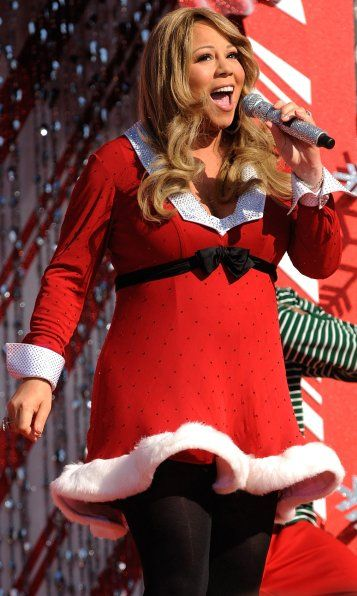 """Mariah Carey, American pop singer recently seen wearing festive red dresses at various events. Pregnant Mariah Carey showed off her growing baby bump in a very fashionable Santa Claus outfit at taping of the 'Disney Parks Christmas Day Parade'. She also performed """"Oh Santa"""" and """"All I Want for Christmas Is You."""""""