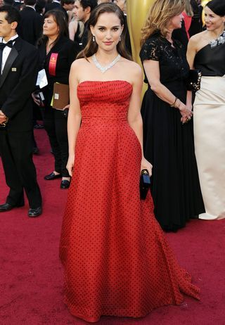 Clad in a polka-dot-red vintage Haute Couture Christian Dior gown from 1954, Natalie Portman is channeling a classic Grace Kelly on the Oscars red carpet.