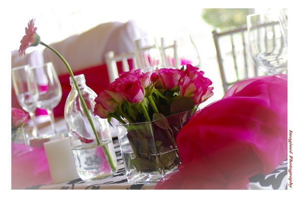We used a variety of glass bottles and vases and filled them with roses and gerberas in cerise pink