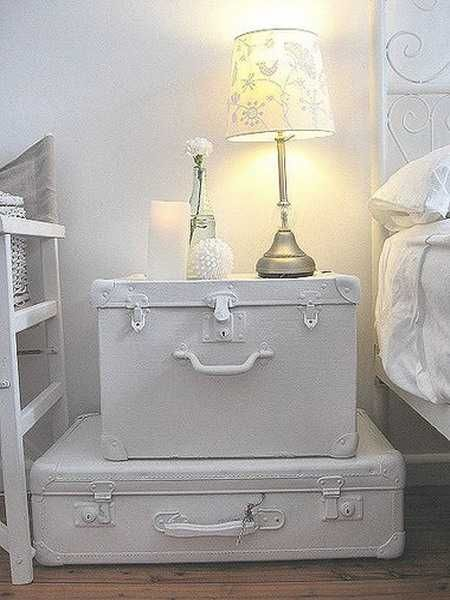 White, painted old suitcases turned into a vintage-style night table.