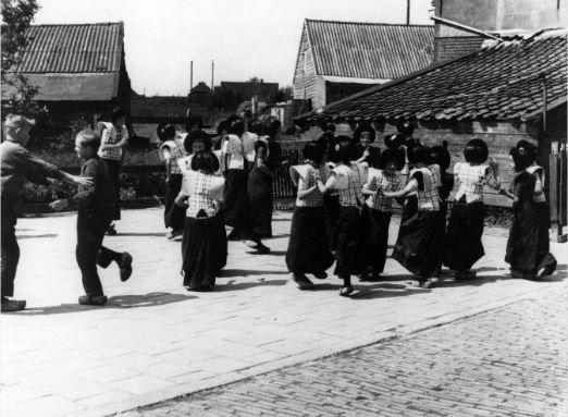 Afbeelding van een groep kinderen in klederdracht tijdens een volksdans op een schoolplein te Eemdijk (gemeente Bunschoten). 1948 WF van Heemskerck Düker (fotograaf) #Utrecht #Spakenburg