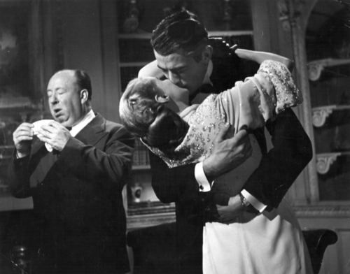 """Alfred Hitchcock in the background while Ingrid Bergman and Gregory Peck kiss on the set of """"Spellbound"""" (1945)"""