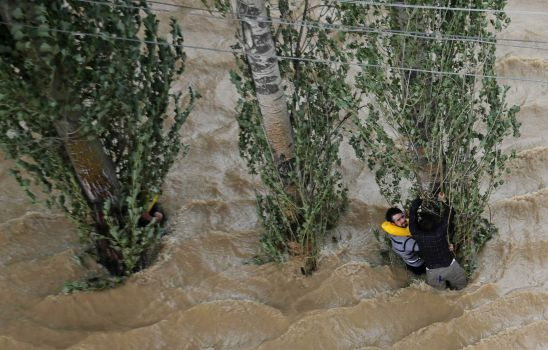 Kashmiris hang on to a tree to prevent being swept away by floodwaters in Srinagar, India, Tuesday, Sept. 9, 2014. The death toll from floods in Pakistan and India reached 400 on Tuesday and have put more than half a million people in peril and rendered thousands homeless in the two neighboring states. Photo: Dar Yasin, AP / AP