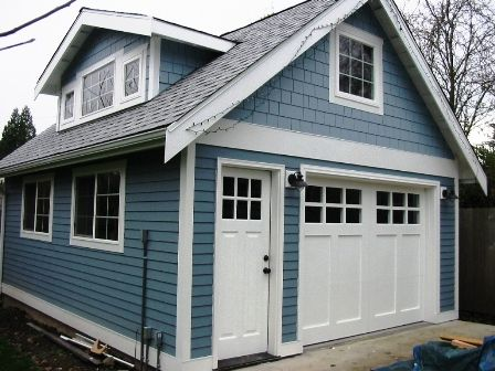 Seattle Custom Garage Doors for a carriage door garage.  Made with a corresponding entry door.  Note the symetrical alignment of all craftsman style door elements.