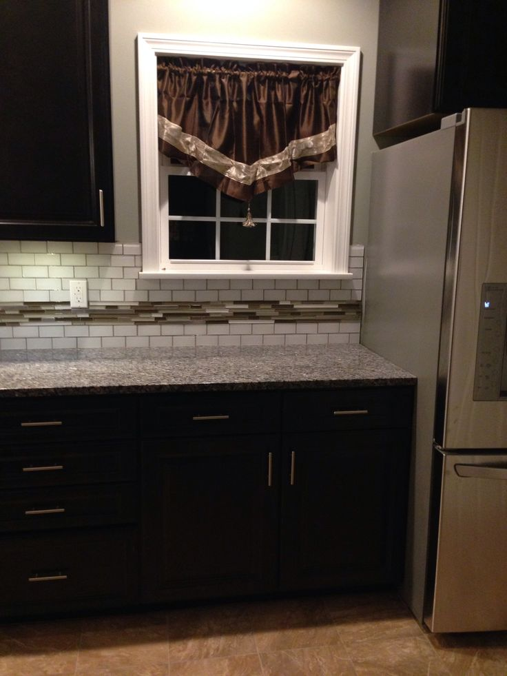Caledonia granite, Polished porcelain tiles and Dark brown cabinets on