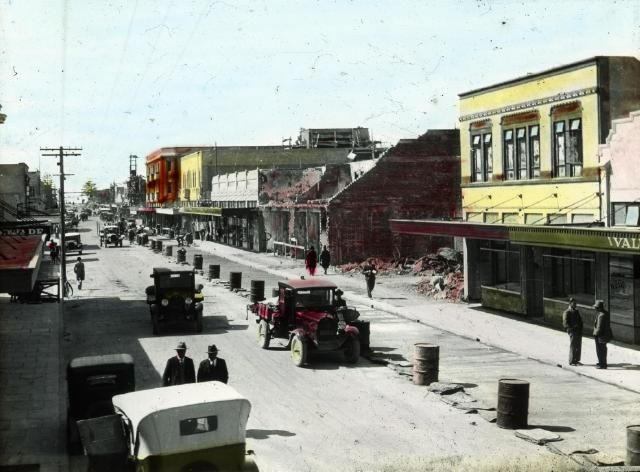 The photograph shows the redevelopment of Emerson Street Napier. The original buildings were destroyed in the 3 February 1931 earthquake and subsequent fire. There are several earthquake damaged buildings visible. New shops have been built and the road is being fixed.  Photographer, possibly Percy Sorrell. Date, unknown.