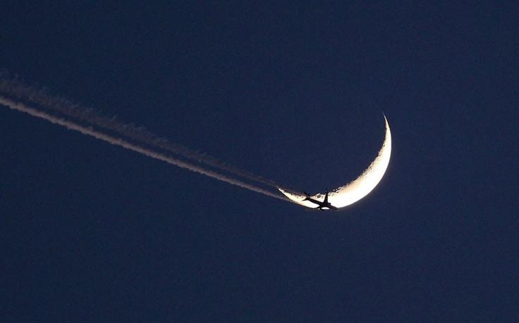 Aircraft flies past a crescent moon.