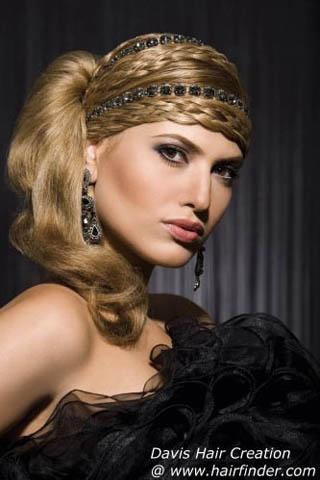 Glamuroso peinado de lujo que remomora épocas pasadas, lleva un turbante realizado con trenzas y mechones de pelo liso adornado con pedrería y un recogido con el pelo hacia el lado en forma de sedosa cola