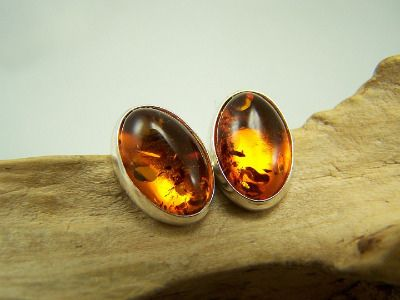 These are largish amber stud earrings in cognac, oval shaped mounted in silver 925.