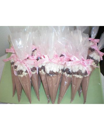 """Hot Cocoa Favors are cake frosting bags filled with hot cocoa mix, white chocolate chips, milk chocolate chips and marshmallows topped off with an 'it's a girl/boy' ribbon,"""""""