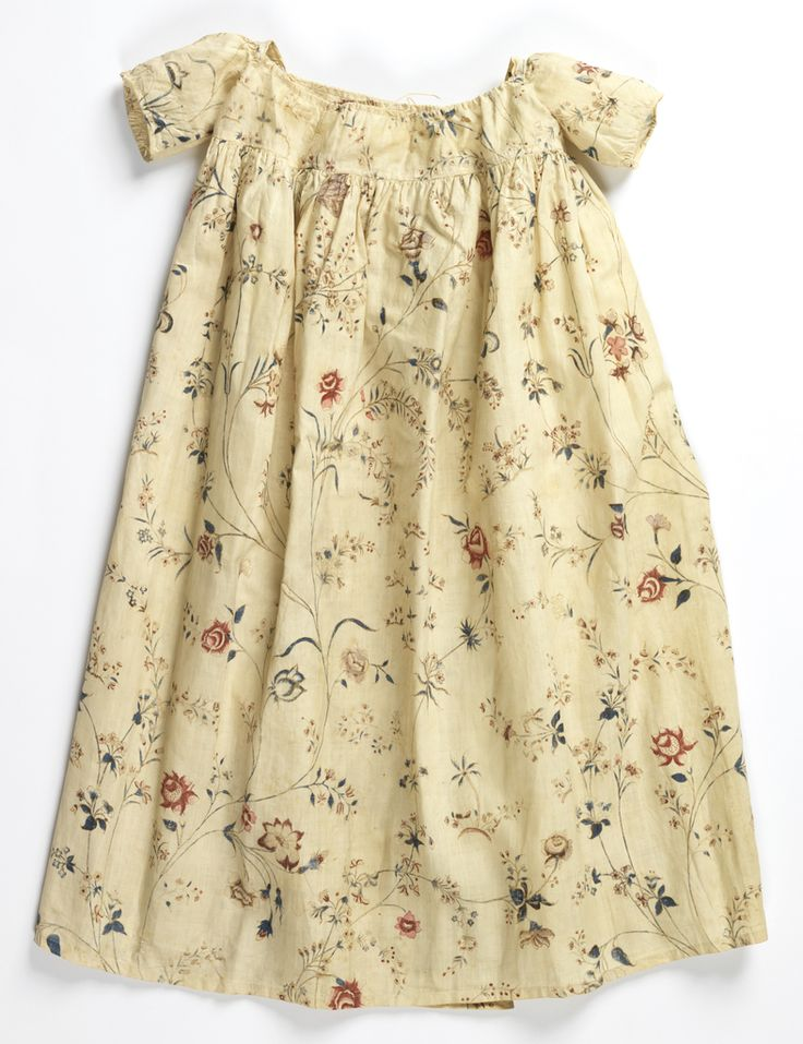 Child's dress, India for the Western market, late 18th century. Cream cotton with a painted pattern of delicate floral sprays in blue, red, lavender and brown.