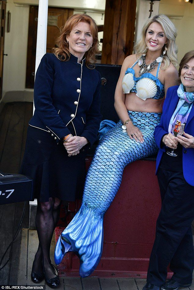 The Duchess of York smiles as she poses for a picture with a woman dressed as a mermaid in Gothenburg, Sweden, on Thursday
