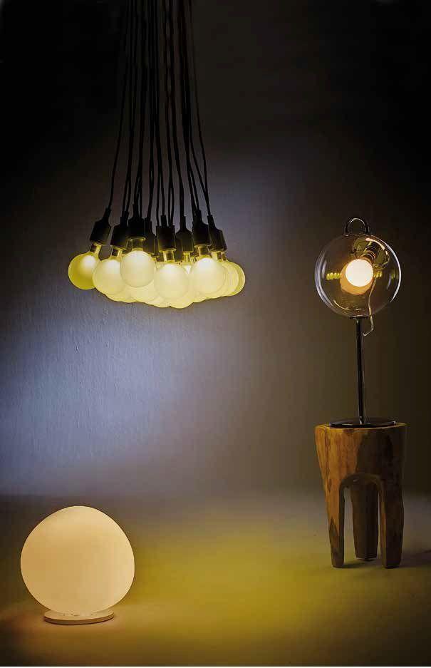 Lámpara de suspensión E27, de 19 luces, diseñada por Matías Stahlbom, en Nordic. Sobre la banca de madera, la lámpara de mesa Miconos, diseñada por Ernesto Gismondi para Artemide.