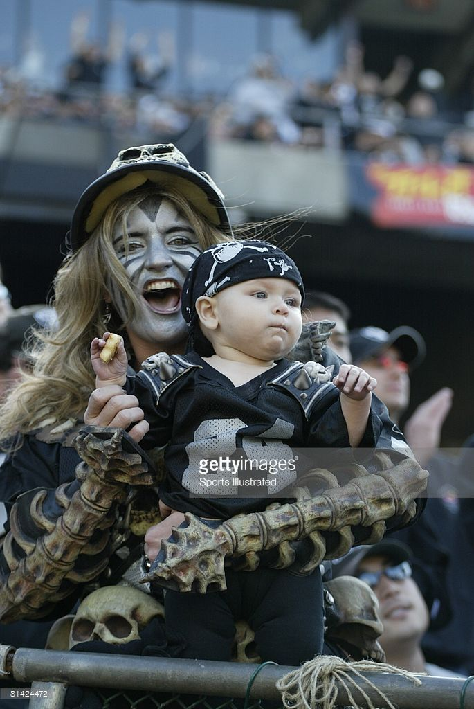 Closeup of painted Oakland Raiders fans in Black Hole during game vs San Diego Chargers, Oakland, CA