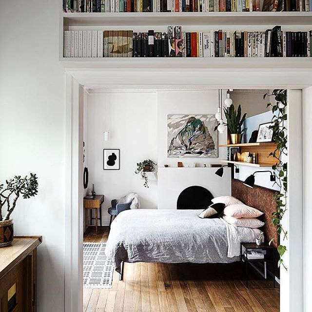wooden floors, grey sheets, book shelves, black sconces, wooden headboard