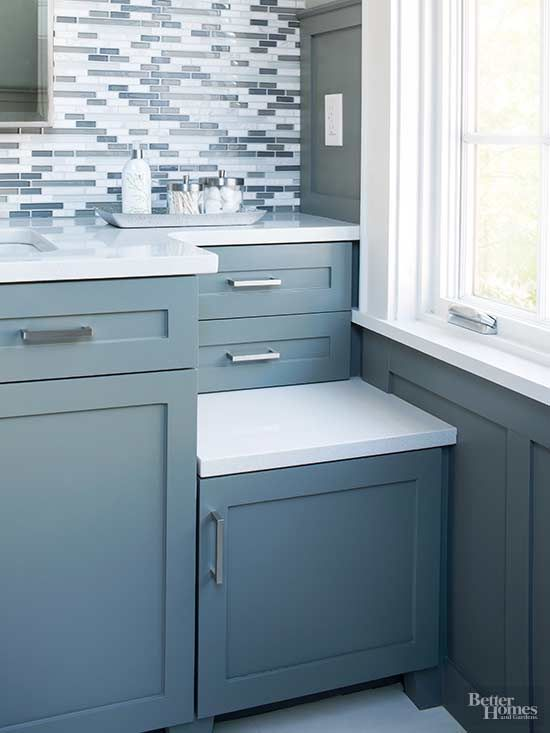 A section of the vanity top was set lower to avoid shortening the window. The dropped-down portion is ideal for touching up a pedicure. The shallow drawers above hold small toiletries, while the low drawer corrals spa-day supplies./