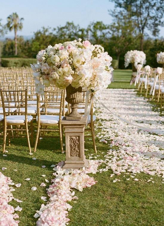 Cerimonia nel giardino, con petali a terra bianchi e rosa, sedie color oro e, all'ingresso, due grandi vasi colmi di fiori bianchi e rosa