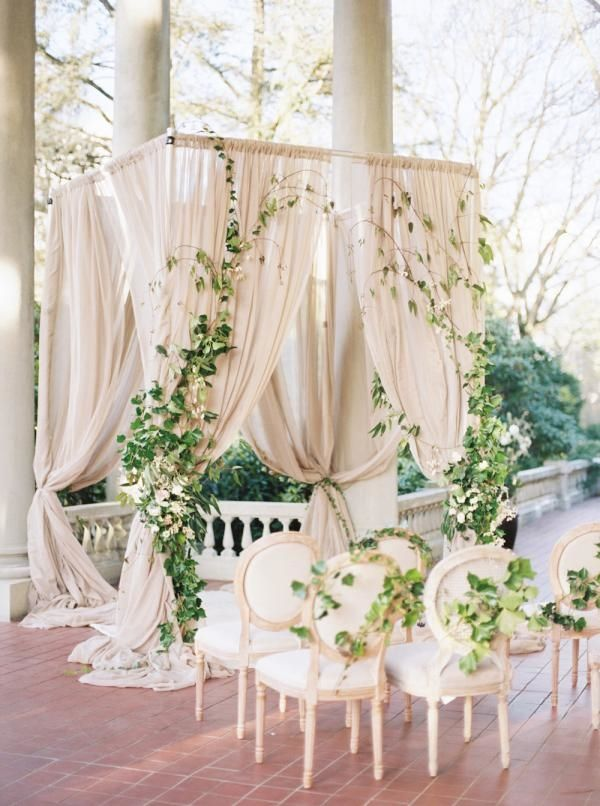 """Elegant Vines: For this patio wedding ceremony, this arch has an """"overgrown"""" quality, with the ivy extending from the gauzy curtains to the guests' chairs.  Also notice the extra long draperies pooling at the bottom of the arch for a dramatic touch."""