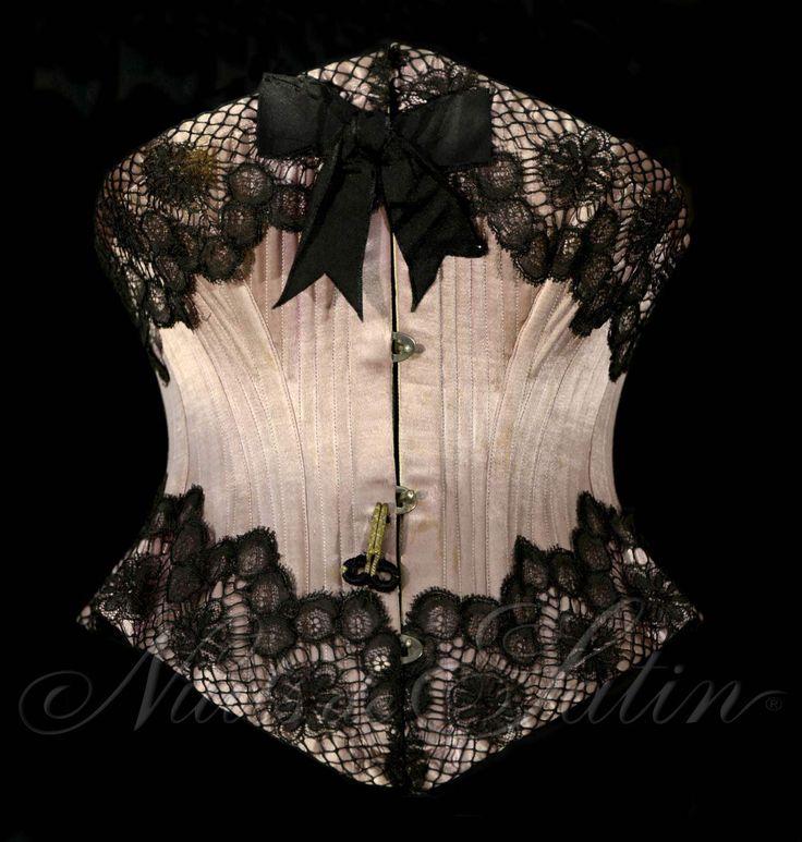 """Corset ceinture en satin mauve 1890' de marque """"LEOUZON""""  , orné d'une dentelle noire sur le haut et le bas, gorge baleinée, doublé et comportant  46 baleines - Busc de 25 cm avec 4 attaches - Tour de taille 48 cm. Collection Nuits de Satin"""