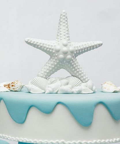 Complement a beach themed wedding with this sophisticated starfish cake  topper. Pure white with white shells at its base. White bisque finish.