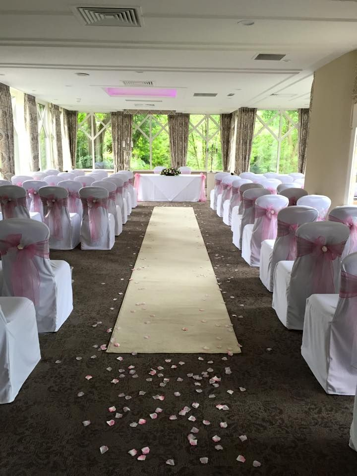 Crabwall Manor Wedding in cheshire, white cotton chair covers with organza sashes and pearl brooches. Ivory aisle runner and petals