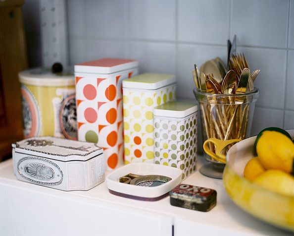 Eclectic Vintage Kitchen Patterned storage tins and a glass of gold flatware in a kitchen Details: White Eclectic-Vintage Kitchen