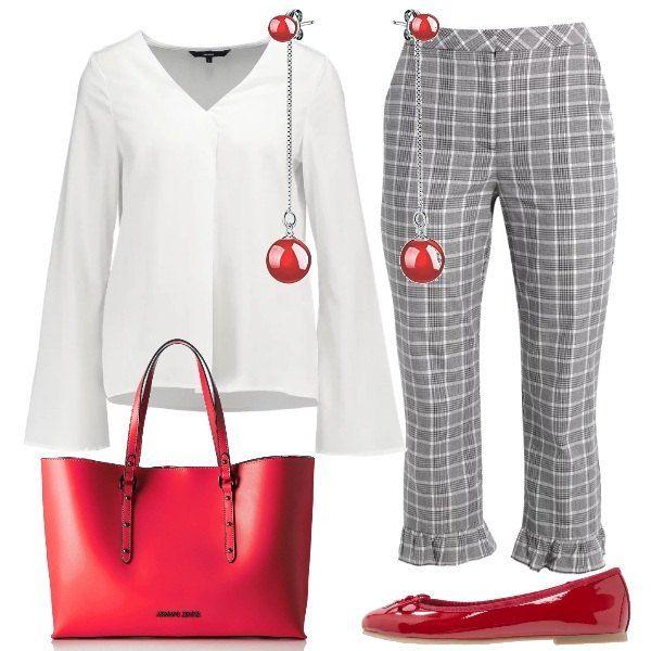 Il rosso dei dettagli accompagna il bianco della camicia con maniche ampie e dei quadretti dei pantaloni con volants allorlo. Le scarpe sono delle ballerine classiche con fiocco, rosse come la borsa e gli orecchini con piccole gocce.