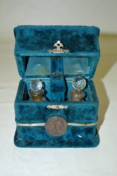 """*1800s  Blue Velvet Box Cask with Crystal Perfume Bottles bronze plaques on lid and front of box, the one on the lid depicts a hunter and rifle with a pheasant and rabbit, The one on the front of the box has a man and woman. (plaques measure 1 3/4-3"""" tall) The plaque on the front is a little loose, there is some wear to the velvet and scrapes in it. The inside of the box is blue satin with velvet covered hinge."""